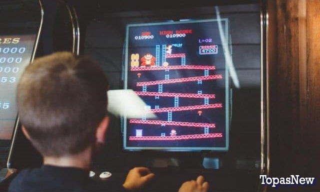 Мальчик играет на игровом автомате - картинка