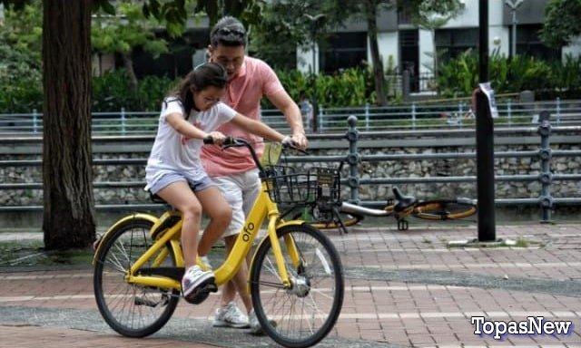 Отец учит дочь кататься на велосипеде - картинка