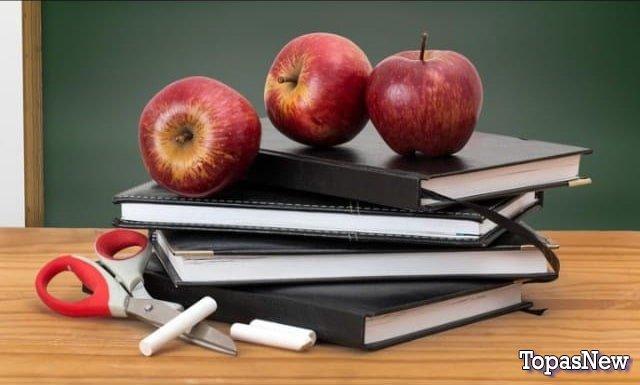 Тетради и яблоки на столе в школе - картинка